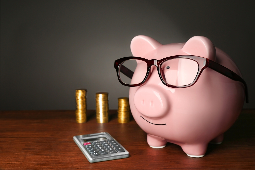 Piggy bank with glasses,coins and calculator on table ,gray background